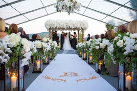 Bride and groom under chuppah antler and orchid aisle runner with monogram and lanterns greenery
