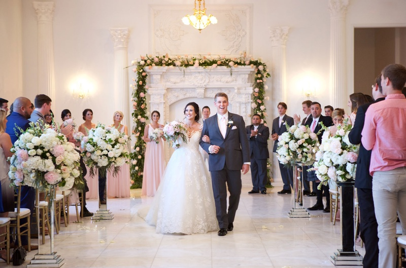 Bride in wedding dress groom in grey suit linking arms flower arch fireplace mirror risers