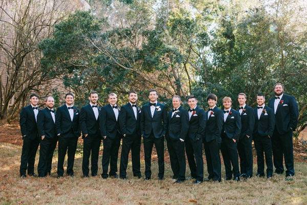 groom with groomsmen wearing suits and bow ties red boutonniere holiday wedding