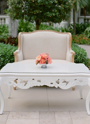 Wedding cocktail hour white coffee table ornate legs pink coral flowers settees courtyard cocktails
