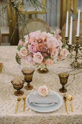 soft champagne-colored linen with embroidery and gold dinnerware low rose centerpiece candelabrum