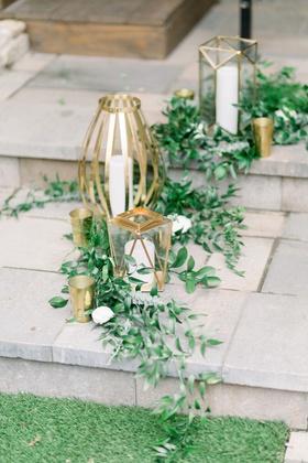 italian ruscus at base of unique gold lanterns