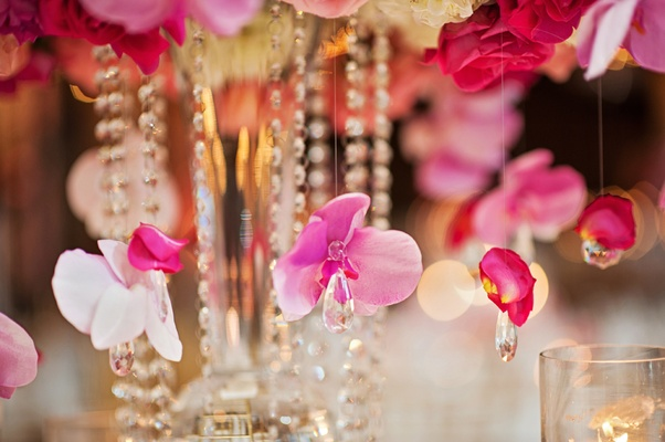 pink orchids hanging from centerpieces with crystal