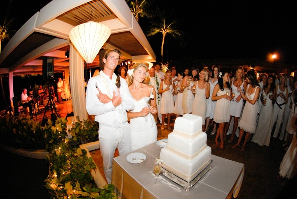 Guests watching bride and groom cut white cake