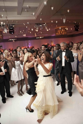 Wedding attendees dancing on white ballroom