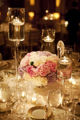 Candlelit wedding reception with peony and rose flower arrangement
