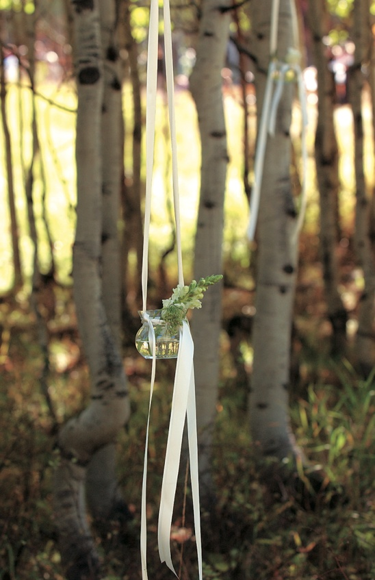 Glass vase filled with florals and ribbons