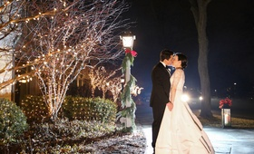 Bride in Oscar de la Renta wedding dress kissing groom at night around Christmas decorations