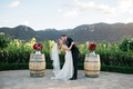 bride and groom kiss outside on vineyard alfresco barrels red and purple flowers california
