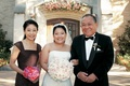 bride stands with father and mother holding pink bouquet