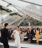 bride changed into one shoulder white jumpsuit for dance clear tent string lights black white floor