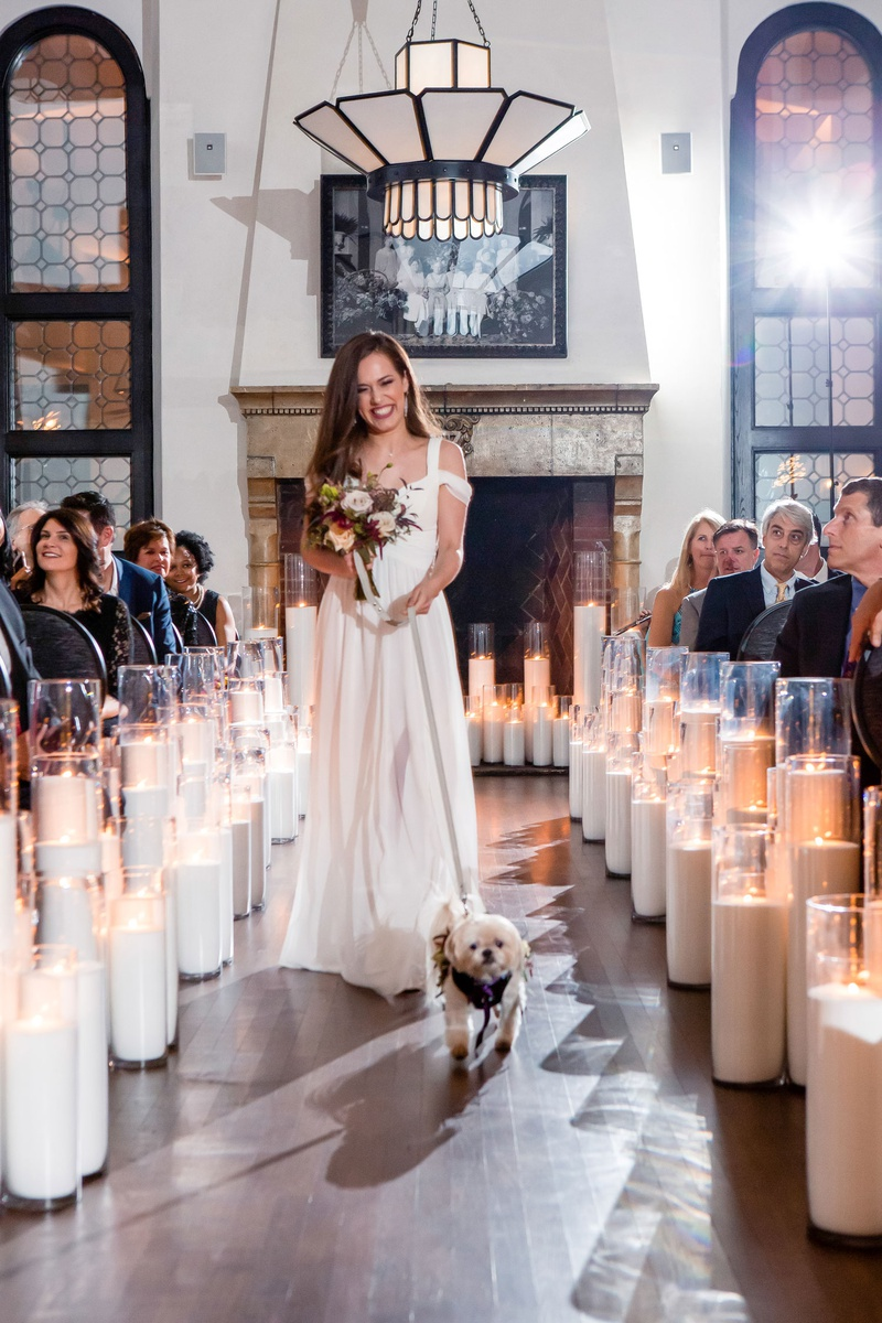 bridesmaid in off shoulder white bridesmaid dress fall bouquet walking little dog down aisle candles
