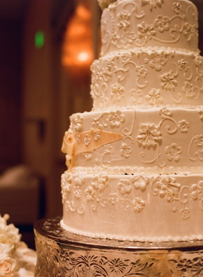 White wedding cake decorated with flowers and filigree