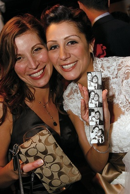 Bride and maid of honor pose with photobooth picture