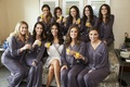 bride in white robe, bridesmaids in dusty purple pajama sets, mimosas while getting ready