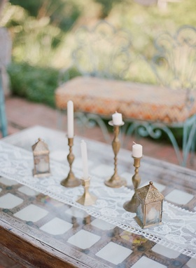 Wedding rehearsal dinner welcome party wood table with white lace runner bronze lantern and candles