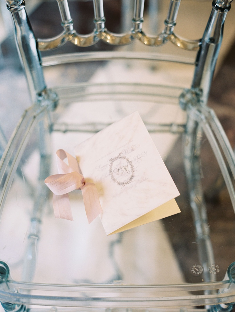 Clear chiavari chair with ceremony program on seat pink ribbon monogram on front oval shape