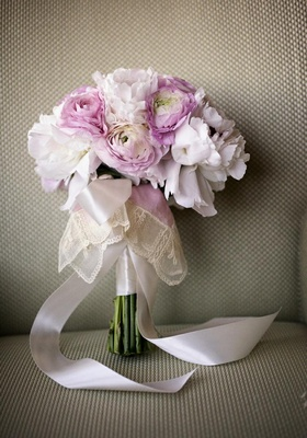 Pink peony and ranunculus flowers tied with lace