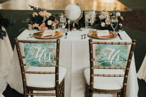 "gold chiavari chairs marked with ""mr."" and ""mrs."" signs made from maps"