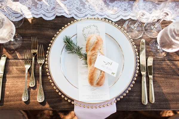 French Baguette with place card on top of wedding menu and rosemary wood table lace runner gold
