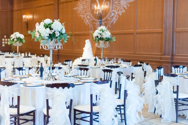 Lighting projection of monogram on wall round tables tall centerpieces white chair covers ruffles