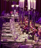 Tall candlesticks on wedding table with purple orchid and rose flowers