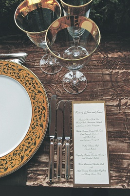 Reception place setting with a golden bordered plate and glasses and menu with script font