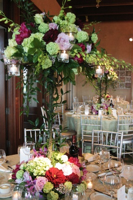 Tall flower centerpiece with green, red, and lavender flowers at its base and on top