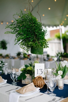 Wedding reception with navy blue table runner, rope sphere, and greenery centerpiece