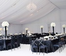 White tent with flower centerpieces and black linens and chairs