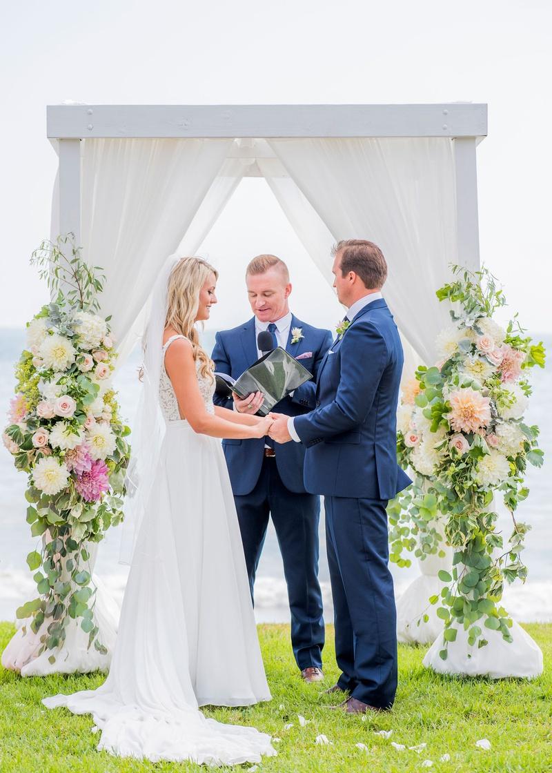 wedding ceremony ocean view green bluff white structure drapery dahlia rose greenery eucalyptus