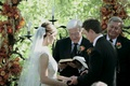 Bride in a lace Monique Lhuillier gown and groom in a black tuxedo with officiants