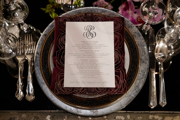 wedding menu framed by dark laser-cut rose pattern on charger plate with black and grey marble rim