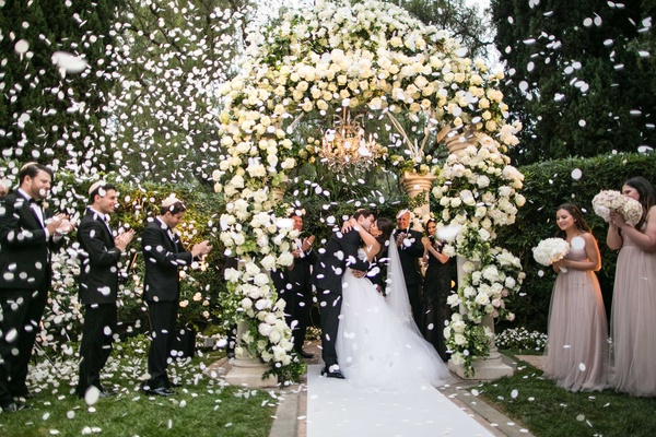 Bride and groom kissing during wedding ceremony with white flower petals exploding in celebration