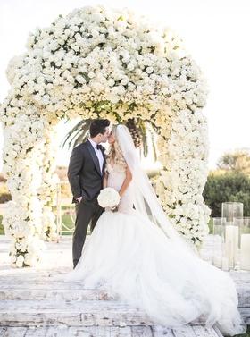 Bride in galia lahav mermaid wedding dress kissing groom in front of canopy of white flowers