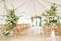 Tan wedding chairs white cushions, green arch, white flower and greenery entrance to aisle