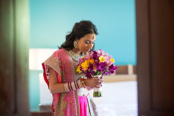 Indian bride in a gold, fuchsia sari holds a bouquet of yellow roses, calla lilies, and pink orchids
