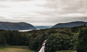 bride and groom in front of sweeping views of field, trees, lake, and hills