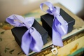 Two small black boxes are tied with light purple ribbon bows for wedding guests on jewelry box