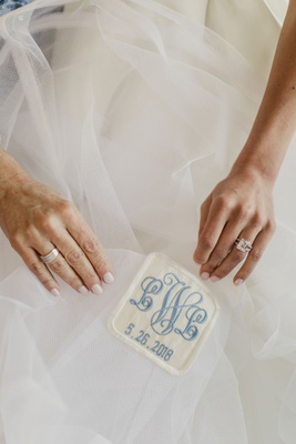 bride with wedding ring holding patch of grandmother's wedding dress sewn into gown blue monogram