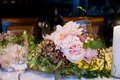 Wedding reception table with pink garden roses, dahlias, green hydrangeas with touches of red