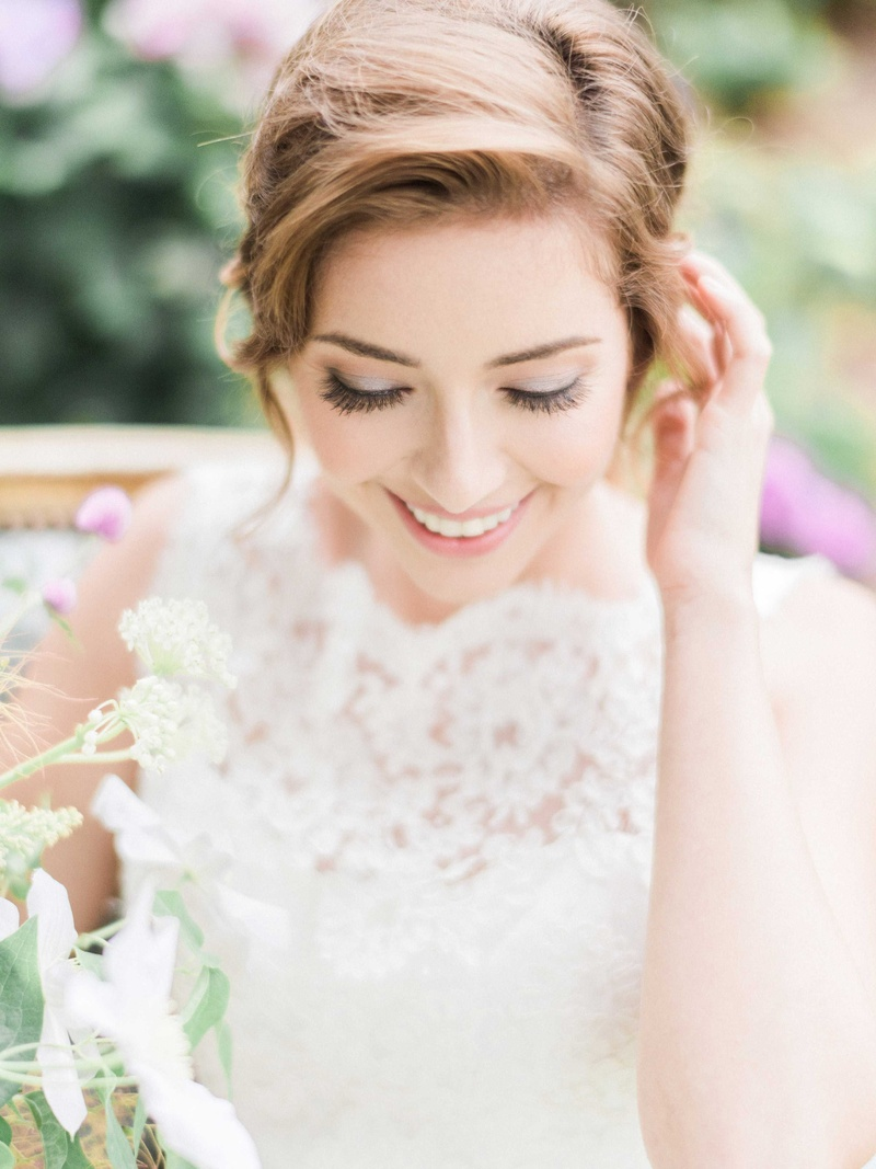 Bride with ponytail hairstyle and boat neck lace wedding dress natural makeup long eyelashes lashes