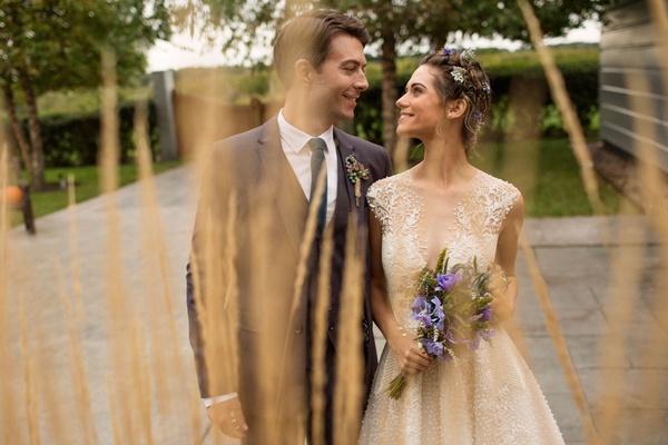 Nikita actors Lyndsy Fonseca and Noah Bean wedding day purple bouquet flowers in hair vineyard