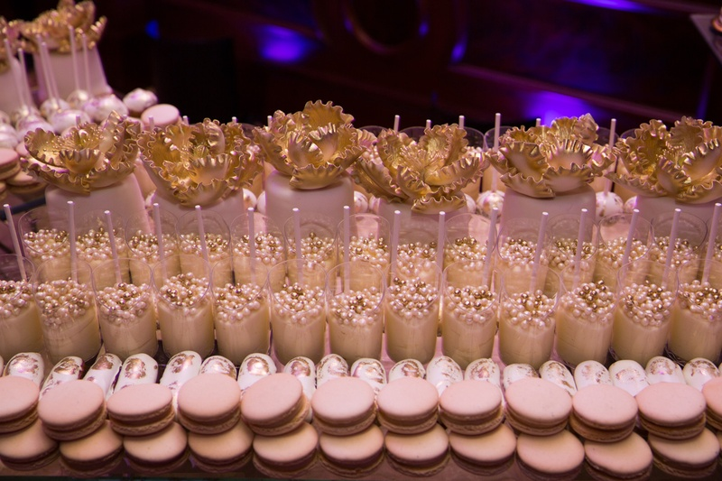 Wedding dessert table with macarons, small cakes with golden fondant peonies, pudding cups with bead