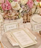 Wedding reception place setting with clear charger with ringed rim, white silk napkin, laser-cut men