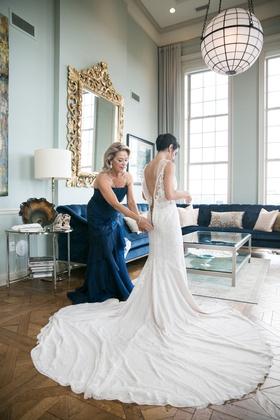 mother of the bride in blue dress zips up bride in rivini wedding dress