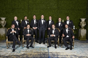 groom in j. hilburn tuxedo with groomsmen in front of wall of greenery