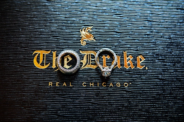wedding rings bands on top of blue and gold label for the drake hotel in chicago