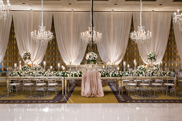 wedding reception decor drapery chandelier long head table mirror clear chairs high low centerpieces