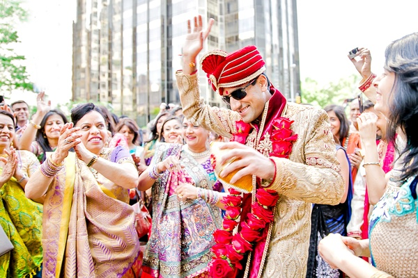 indina-american groom dances with guests during baraat, grand entrance